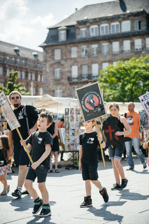 outcry: STRASBOURG, FRANCE - AUG 22, 2015: Marine conservation non-profit organization Sea Shepherd protesting against the slaughter of pilot whales and arrest of 7 crew members - kids holding placards