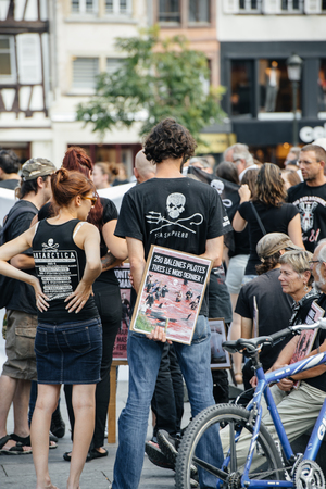 outcry: STRASBOURG, FRANCE - AUG 22, 2015: Marine conservation non-profit organization Sea Shepherd protesting against the slaughter of pilot whales and arrest of 7 crew members - man with placard