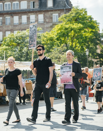 outcry: STRASBOURG, FRANCE - AUG 22, 2015: Marine conservation non-profit organization Sea Shepherd protesting against the slaughter of pilot whales and arrest of 7 crew members - solidarity group holding placards