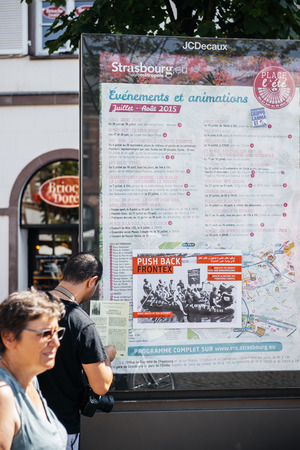 outcry: People protesting against immigration policy and border management which asks for commitment in the wake of migrants boat disasters - man putting placards on public map