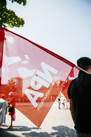 outcry: People protesting against immigration policy and border management which asks for commitment in the wake of migrants boat disasters - new anticapitalist party flag