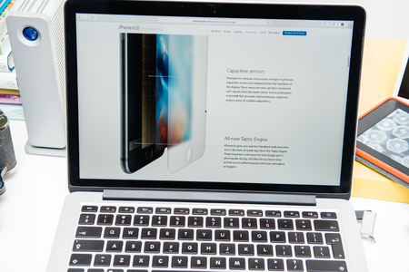 unveiling: PARIS, FRANCE - SEP 9, 2015: Apple Computers website on MacBook Pro Retina in a creative room environment showcasing the newly announced iPhone 6s and its screen