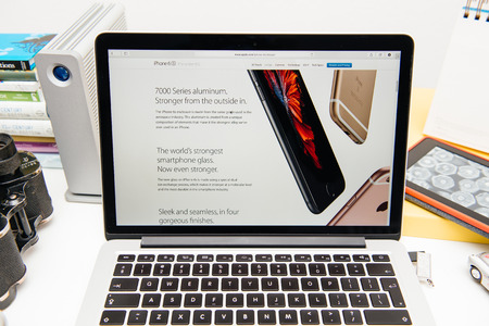 announced: PARIS, FRANCE - SEP 9, 2015: Apple Computers website on MacBook Pro Retina in a creative room environment showcasing the newly announced iPhone 6s and its finishes