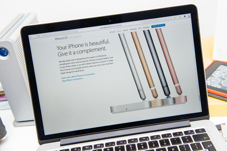 announced: PARIS, FRANCE - SEP 9, 2015: Apple Computers website on MacBook Pro Retina in a creative room environment showcasing the newly announced iPhone 6S and its charging dock