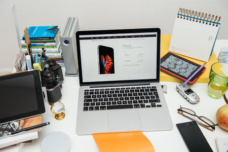 announced: PARIS, FRANCE - SEP 9, 2015: Apple Computers website on MacBook Pro Retina in a creative room environment showcasing the newly announced iPhone 6S and its price