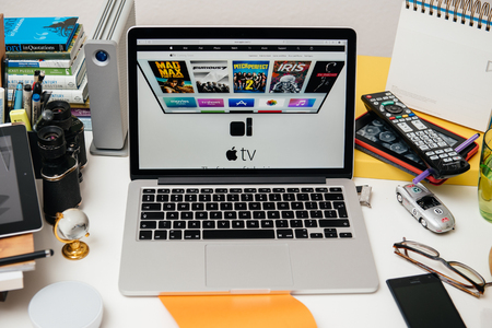 apple computers: PARIS, FRANCE - SEP 10, 2015: Apple Computers website on MacBook Pro Retina in a creative room environment showcasing the newly announced Apple TV - the future of television