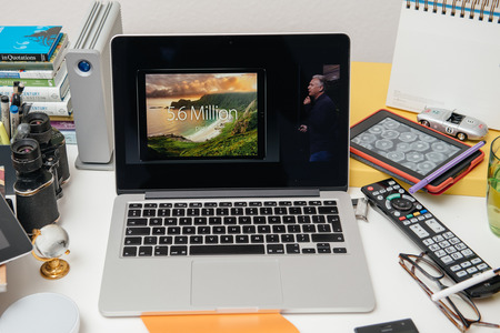 apple computers: PARIS, FRANCE - SEP 10, 2015: Apple Computers website on MacBook Pro Retina in a creative room environment showcasing Philip Schiller from Apple talking about resolution of iPad Pro