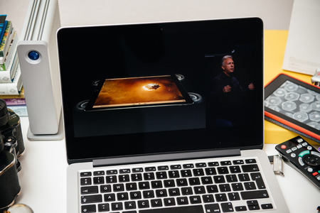 apple computers: PARIS, FRANCE - SEP 10, 2015: Apple Computers website on MacBook Pro Retina in a creative room environment showcasing Philip Schiller from Apple talking about audio system of iPad Pro
