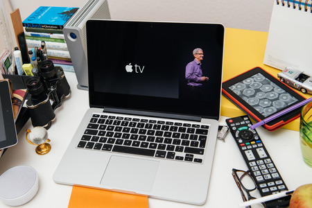 PARIS, FRANCE - SEP 10, 2015: Apple Computers website on MacBook Pro Retina in a creative room environment with Tim Cook and New Apple TV Редакционное