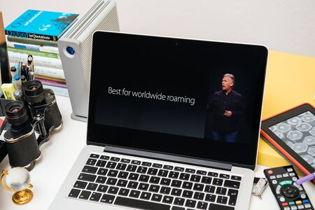 announced: PARIS, FRANCE - SEP 10, 2015: Apple Computers website on MacBook Pro Retina in a creative room environment showcasing the newly announced iPhone 6 with roaming options