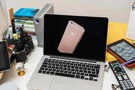 apple computers: PARIS, FRANCE - SEP 10, 2015: Apple Computers website on MacBook Pro Retina in a creative room environment showcasing the newly announced iPhone 6s Plus in golden pink rose