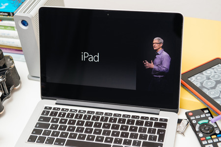 announced: PARIS, FRANCE - SEP 10, 2015: Apple Computers website on MacBook Pro Retina in a creative room environment with Tim Cook and iPad Editorial