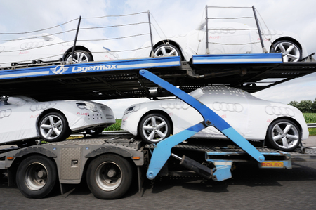 commercialization: INGOLSTADT, GERMANY - JULY 04, 2011: Audi sport cars being transported on a Lagermax Trailer near Ingolstadt, Germany. Lagermax is one of the biggest transportation company in Europe