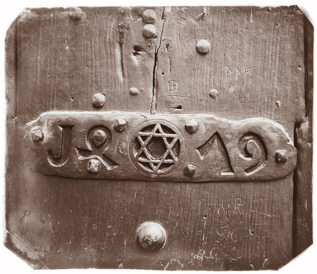 zionism: Closeup of an door with Star of David into a steel frame placed on textured colorful old wood.