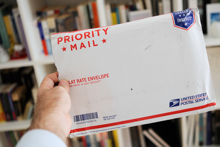 usps: LONDON, UNITED KINGDOM - OCTOBER 18, 2014: USPS United States Postal Service Parcel envelope in mans hand displaying damaged documents on boockself background. The United States Postal Service, also known as the Post Office, U.S. Mail, or Postal Service,