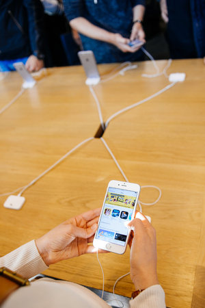 app store: PARIS, FRANCE - OCT 3, 2015: Customer checks the new iPhone 6s displayed at the Apple Store Opera with the Games App Store