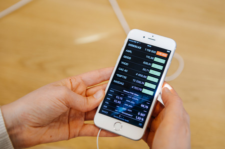 stock quotations: PARIS, FRANCE - OCT 3, 2015: Customer checks the new iPhone 6s Plus displayed at the Apple Store Opera with the Apple Stock App checking financial quotations