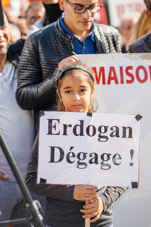 young leave: STRASBOURG, FRANCE - OCT 4, 2015 Demonstrators protesting against Turkish President Recep Tayyip Erdogans visit to Strasbourg - young girl holding Erdogan, leave! placard Editorial