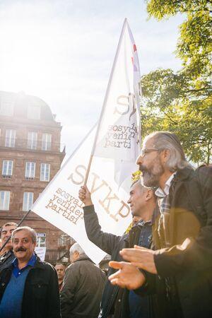 demonstrators: STRASBOURG, FRANCE - OCT 4, 2015 Demonstrators protesting against Turkish President Recep Tayyip Erdogans visit to Strasbourg - man holding flag of Socialist Party of Refoundation