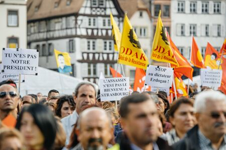 demonstrators: STRASBOURG, FRANCE - OCT 4, 2015 Demonstrators protesting against Turkish President Recep Tayyip Erdogans visit to Strasbourg - crowd waving flags and placards in Place Kleber
