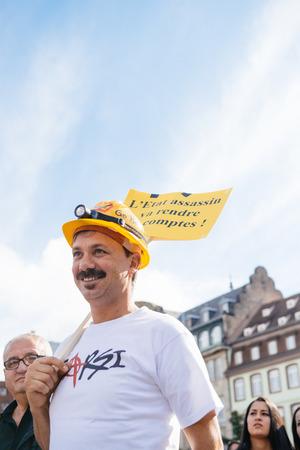 demonstrators: STRASBOURG, FRANCE - OCT 4, 2015 Demonstrators protesting against Turkish President Recep Tayyip Erdogans visit to Strasbourg - worker with helmet  holding anti  Erdogan placard