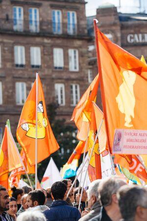 demonstrators: STRASBOURG, FRANCE - OCT 4, 2015 Demonstrators protesting against Turkish President Recep Tayyip Erdogans visit to Strasbourg - crowd waving red flags Editorial