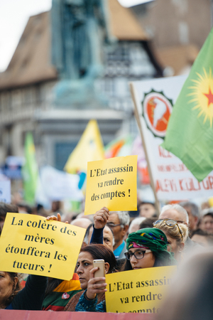 demonstrators: STRASBOURG, FRANCE - OCT 4, 2015 Demonstrators protesting against Turkish President Recep Tayyip Erdogans visit to Strasbourg - the anger of mothers will suffocate killers placard in womens hands