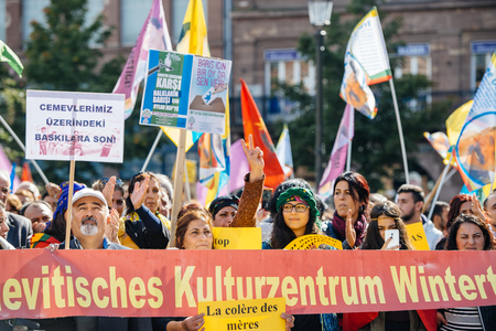 demonstrators: STRASBOURG, FRANCE - OCT 4, 2015 Demonstrators protesting against Turkish President Recep Tayyip Erdogans visit to Strasbourg - members of the Alevi community holding placards Editorial