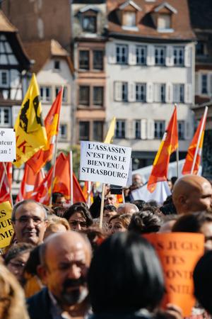 demonstrators: STRASBOURG, FRANCE - OCT 4, 2015 Demonstrators protesting against Turkish President Recep Tayyip Erdogans visit to Strasbourg - The killer is not welcome to Strasbourg placard