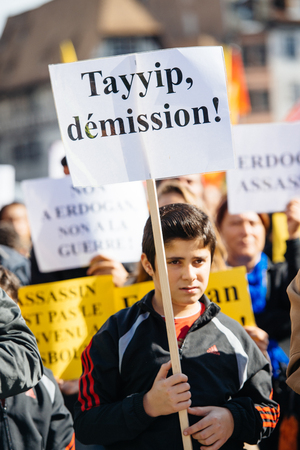 demonstrators: STRASBOURG, FRANCE - OCT 4, 2015 Demonstrators protesting against Turkish President Recep Tayyip Erdogans visit to Strasbourg - Tayyip, resign now placard in boys hand