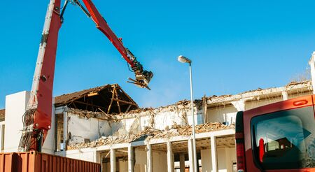 deconstruct: Building demolition by a heavy twisted rebars industrial machine on a red truck