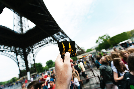 eiffel tower architecture: PARIS - JULY 12: Tourist hand is holding two access tickets to Eiffel Tower from Paris, France.The Eiffel tower is the most visited monument of France and probably in the world
