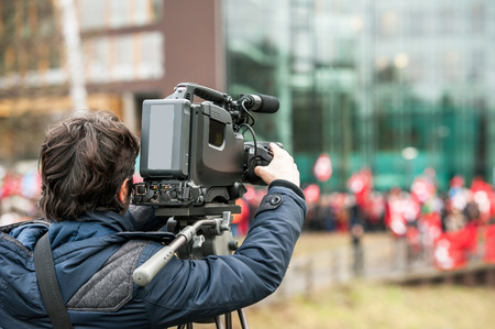 historic world event: Camera operator working outside during breaking news live event - streaming via its camera Stock Photo