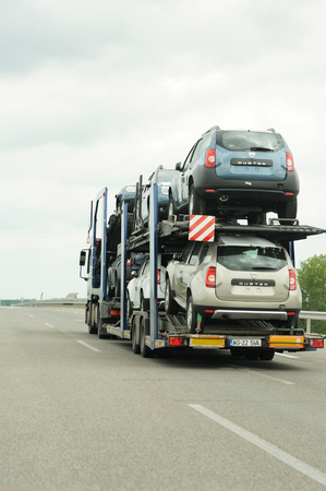 transported: ROMANIA - JULY 04, 2011: Dacia Duster cars being transported on a Lagermax Trailer near Hungarian border. Dacia is a Romanian car maker owned by renault Editorial