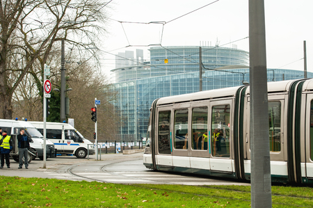 european parliament: STRASBOURG, FRANCE - JANUARY 28, 2015: Tramway in front of European Parliament building with police van and officers surveying adjacent area