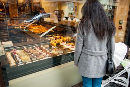 madre soltera: ESTRASBURGO, FRANCIA - 10 DE ENERO DE, 2015: La madre soltera admirando alimentos dulces de repostería francesa en el típico salón de panadería francesa Editorial