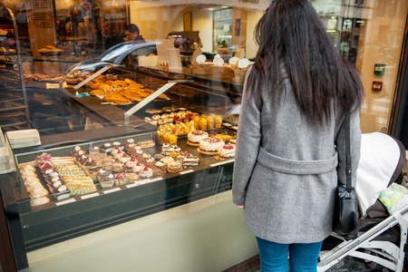 boulangerie: STRASBOURG, FRANCE - JANUARY 10, 2015: Single mother admiring French sweet pastry food in typical French boulangerie saloon
