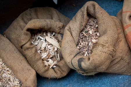 holzbriketts: Material used for pellets - compressed organic matter, or biomass made from sawdust in their organic bags next to eachother Lizenzfreie Bilder