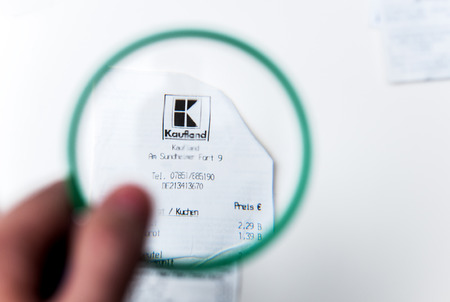 PARIS, FRANCE - JANUARY 14, 2015: Mann looking through a magnifying glass to receipt from Kaufland Store in Germany. The chain operates over 1,000 stores in Germany, Czech Republic, Slovakia, Poland, Romania, Bulgaria and Croatia.