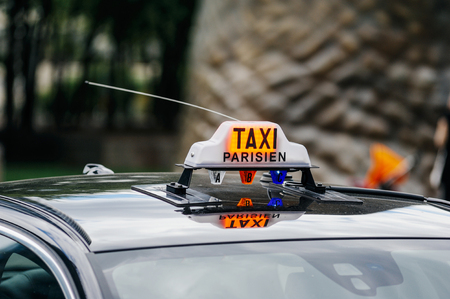 taxi sign: PARIS, FRANCE - JULY 14, 2011: Taxi Parisien - Paris Taxi sing on the roof of a transportation car in French Captial.