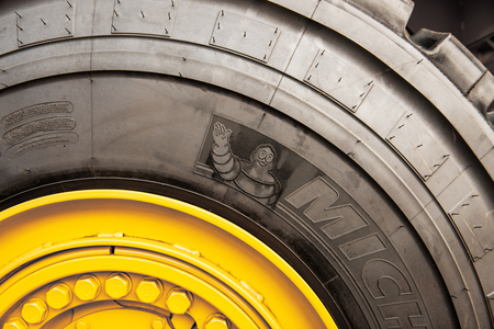 tire: FRANKFURT, GERMANY - SEPTEMBER 05, 2014: Detail of imense Michelin tire on yellow tractor. Michelin is a tire manufacturer based in Clermont-Ferrand in the Auvergne rgion of France. It is one of the three largest tire