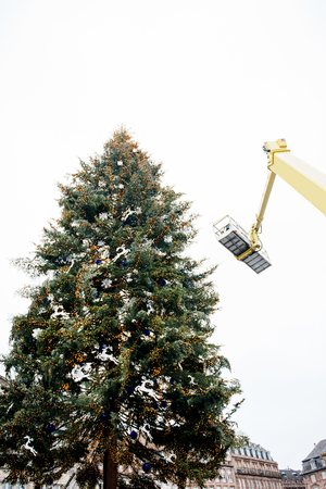 assemblage: Christmas xmas tree assemblage by crane and workers in modern city - France Stock Photo