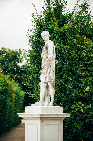 schonbrunn palace: Ancient male statue in Schonbrunn Palace in Vienna, Austria surrounded by vivid green trees through alley Editorial
