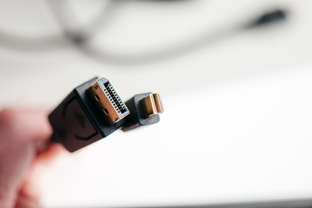 dvi: Hand holding Mini DisplayPort and DisplayPort cables with main focus to the cable connections - tilt-shift lens used Stock Photo