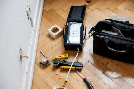optic fiber: Fiber optic instalation - network and spectrum analyzers and other tools on wooden parquet floor next tot electrical and antenna wall sockets just after installation of digital fiber optic cable for high speed internet, telephone and digital UHD televisio Stock Photo