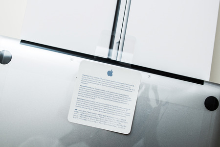 PARIS, FRANCE - JANUARY 14, 2015: Recently launched Apple Macbook Pro Retina laptop unboxing security seal with important notice about software agreement on its cartoon box 新聞圖片