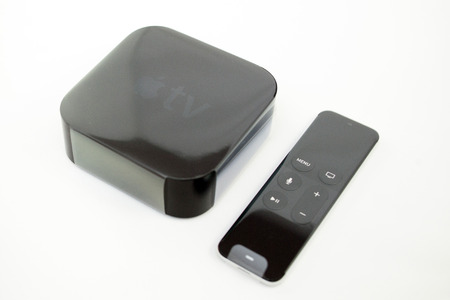 motion sensor: PARIS, FRANCE - NOV 10, 2015: New Apple TV media streaming  player microconsole by Apple Computers - right view plastic film unboxing. It has new touch remote swipe-to-select with integrated Siri and motion sensor