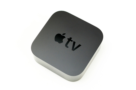 motion sensor: PARIS, FRANCE - NOV 10, 2015: New Apple TV media streaming  player microconsole by Apple Computers - isolated on white perspective view. It has new touch remote swipe-to-select with integrated Siri and motion sensor