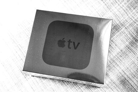 motion sensor: PARIS, FRANCE - NOV 10, 2015: Last Apple TV media streaming player microconsole by Apple Computers - unboxed box on sofa.  It has new touch remote swipe-to-select with integrated Siri and motion sensor