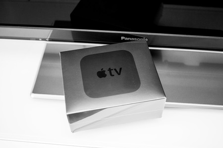 motion sensor: PARIS, FRANCE - NOV 10, 2015: New Apple TV media streaming  player microconsole by Apple Computers - box near Panasonic TV.  It has new touch remote swipe-to-select with integrated Siri and motion sensor Editorial
